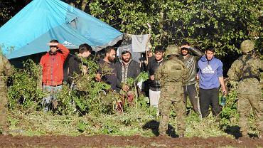 31 sierpnia 2021, Usnarz Górny. Komunikacja z grupą 32 Afgańczyków i Afganek, koczujących na granicy już ponad trzy tygodnie, nie jest łatwa. Pogranicznicy i wojsko odsunęli dziennikarzy i działaczy organizacji humanitarnych na 200-300 metrów od obozowiska, dostępu do niego broni podwójny kordon mundurowych.