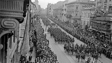 Uroczystości pogrzebowe Józefa Piłsudskiego 17 maja 1935 r. Zdjęcie przedstawia kondukt na Nowym Świecie, w drodze z katedry św. Jana Chrzciciela na Pole Mokotowskie, skąd trumna z ciałem marszałka odjechała pociągiem do Krakowa. Piłsudskiego żegnały tłumy warszawiaków. Na budynkach pojawiły się żałobne dekoracje i czarne flagi, a uliczne latarnie spowite były kirem