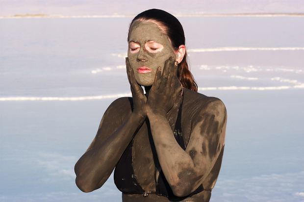 Kobieta okładająca twarz błotem z Morza Martwego - Morze Martwe, Izrael / shutterstock