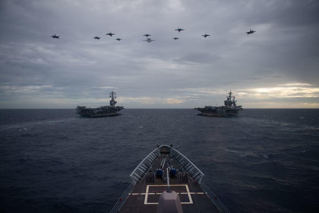 Dwa lotniskowce atomowe, formacja samolotów nad nimi i dziób krążownika rakietowego