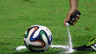 Sędzia wytycza sprayem miejsce, skąd będzie wybijana piłka
