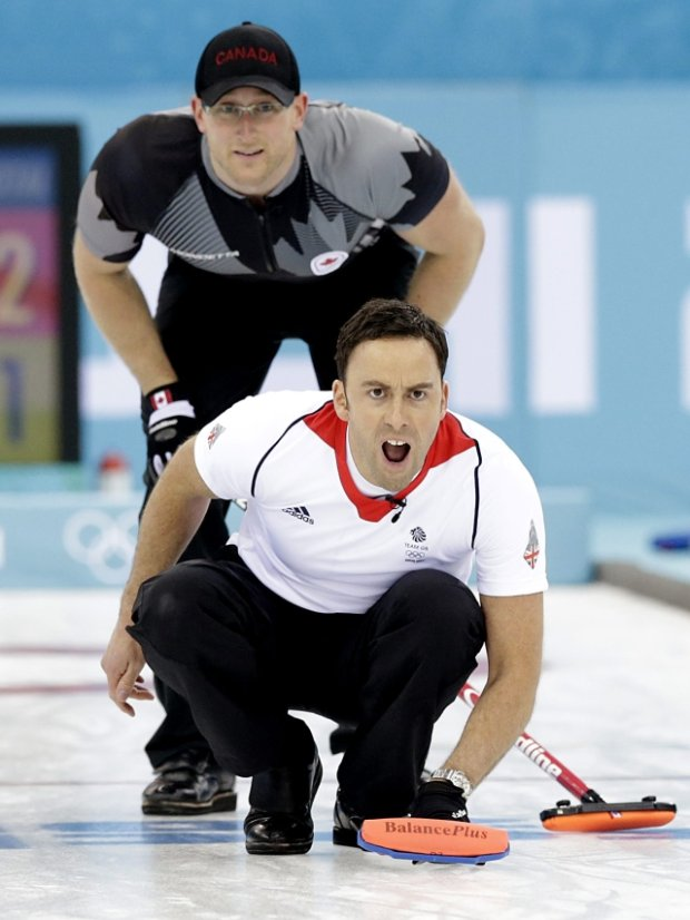 Britain's skip David Murdoch, front, shouts to his teammates while Canada's Ryan Harnden watches the rock during the men's curling gold medal game against Canada at the 2014 Winter Olympics Friday, Feb. 21, 2014, in Sochi, Russia. (AP Photo/Wong Maye-E)