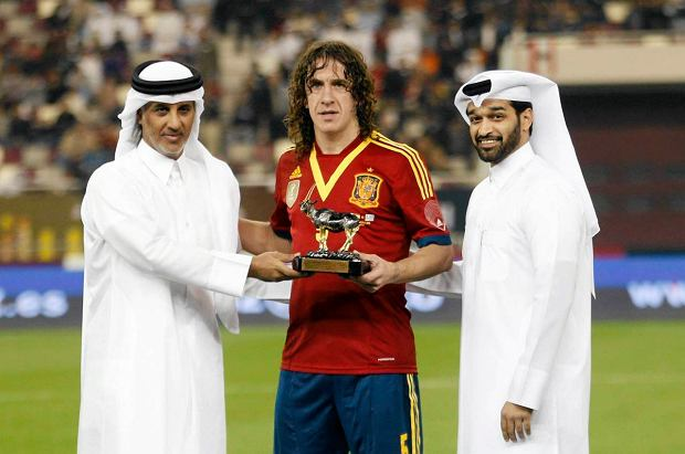 Spain's Carles Puyol (C) receives a trophy for his 100th international game from Qatar Football Association President Sheikh Hamad bin Khalifa Al Thani (L) and 2022 FIFA World Cup Qatar Supreme Committee Secretary-General Hassan Al-Thawadiat at their international friendly soccer match against Uruguay in Doha February 6, 2013. REUTERS/ Fadi Al-Assaad (QATAR - Tags: SPORT SOCCER) SLOWA KLUCZOWE: :rel:d:bm:GF2E9261L8K01
