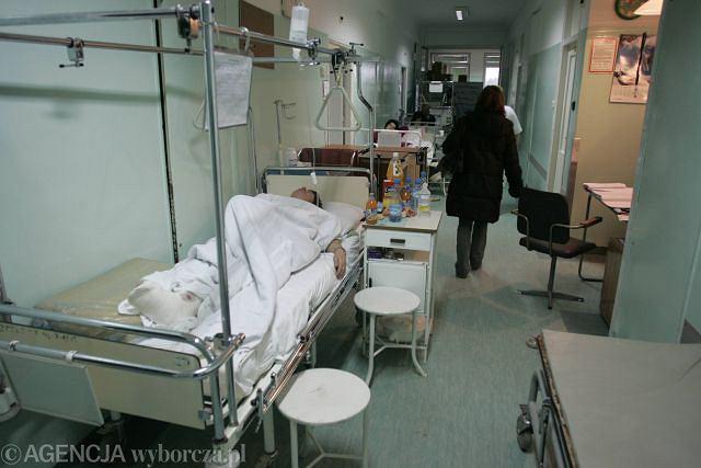 Pacjenci leżący na szpitalnym korytarzu