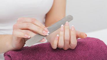 Jak piłować paznokcie? Można wykonać ten zabieg z pomocą tradycyjnego pilnika lub frezarki. Zdjęcie ilustracyjne