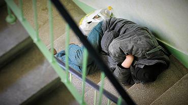 Bezdomny śpiący na klatce schodowej (zdjęcie ilustracyjne)