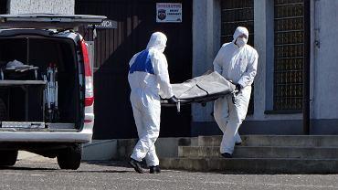 Pracownicy firmy pogrzebowej w strojach ochronnych