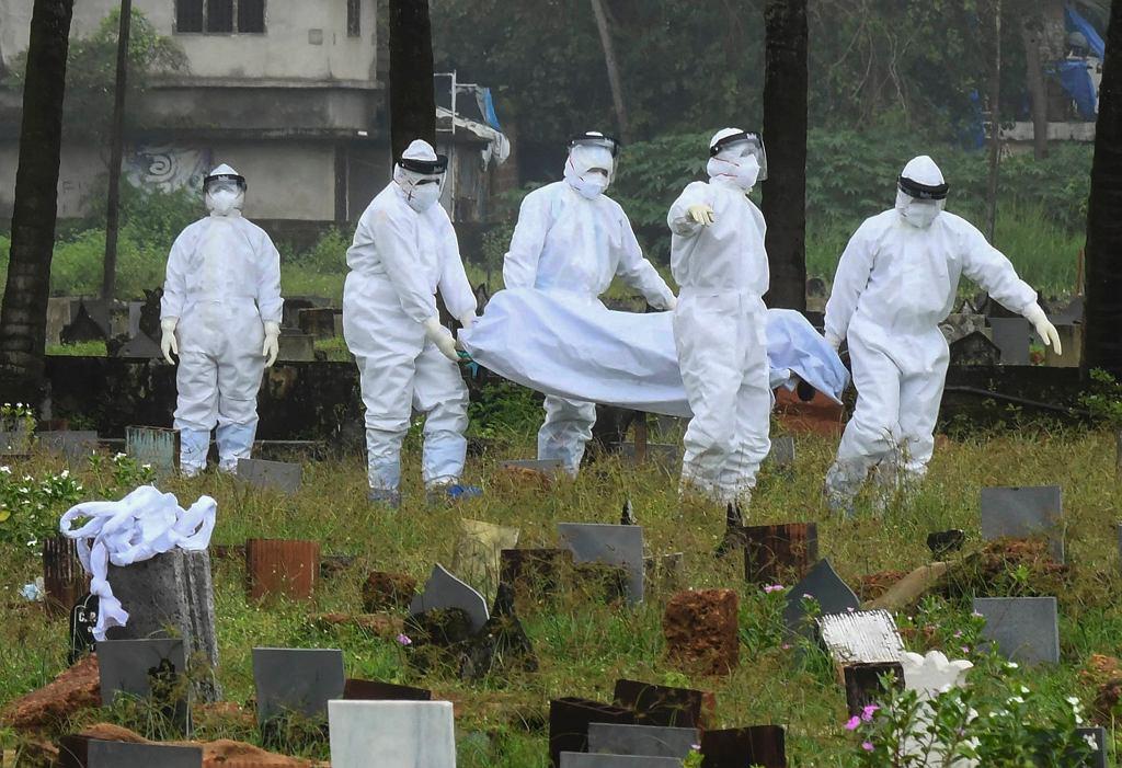 Ludzie w kombinezonach ochronnych przygotowują się do kremacji ciała 12-letniego chłopca zmarłego na wirusa Nipah