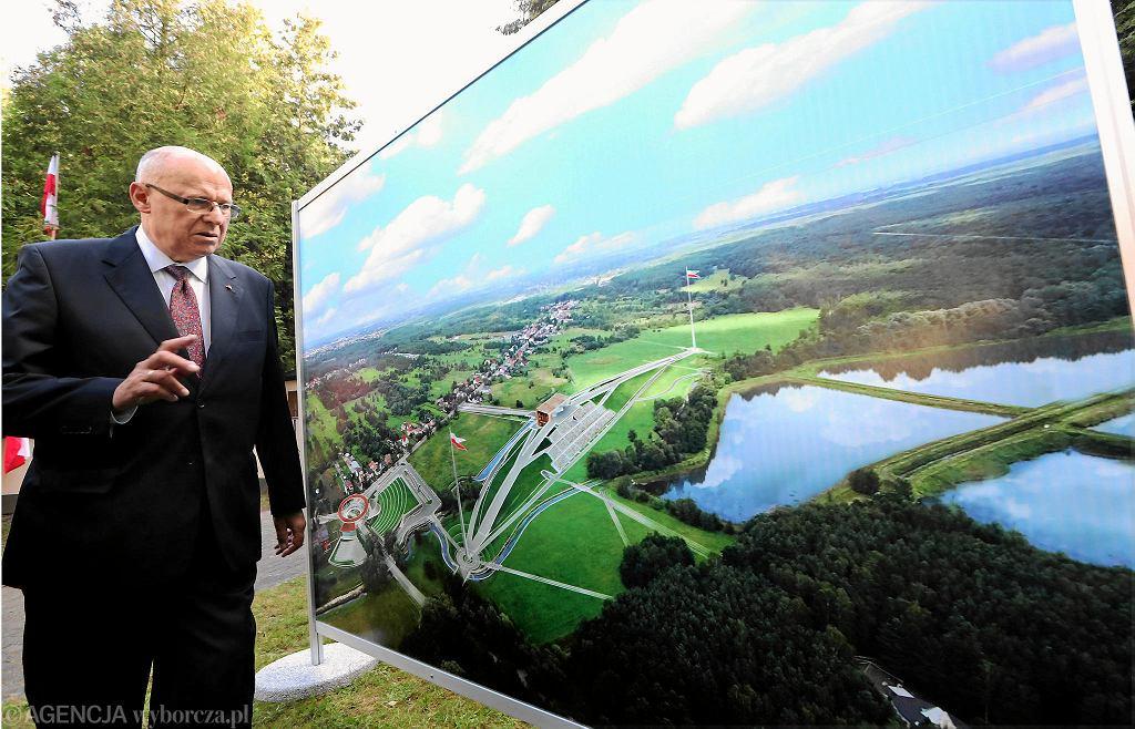 15 sierpnia 2018 r. Czesław Bielecki na tle planszy z wizualizacją jego projektu Muzeum Bitwy Warszawskiej 1920 r. , które miało powstać w Ossowie. Proponowany wówczas obiekt ma zostać pomniejszony.