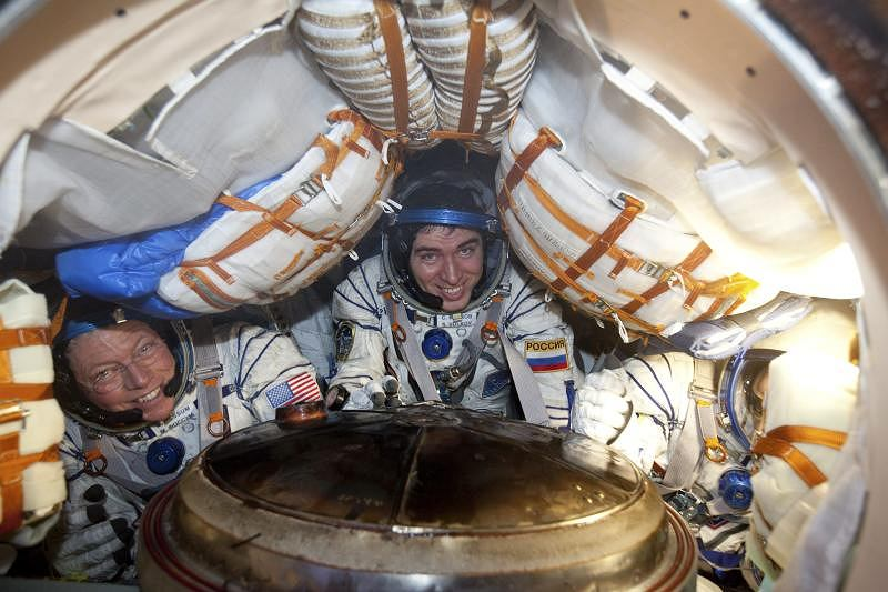 ISS members from left, U.S. astronaut Michael Fossum, Russian cosmonaut Sergei Volkov and Japanese astronaut Satoshi Furukawa smile from inside the Soyuz capsule minutes after they landed near the town of Arkalyk, northern Kazakhstan,Tuesday, Nov. 22, 2011. (AP Photo/Sergei Remizov, Pool)