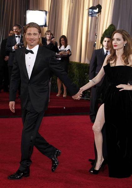 REFILE - CORRECTING MARITAL STATUS    Actor Brad Pitt leads his partner actress Angelina Jolie up the red carpet at the 84th Academy Awards in Hollywood, California, February 26, 2012.   REUTERS/Lucas Jackson   (UNITED STATES) (OSCARS-ARRIVALS)