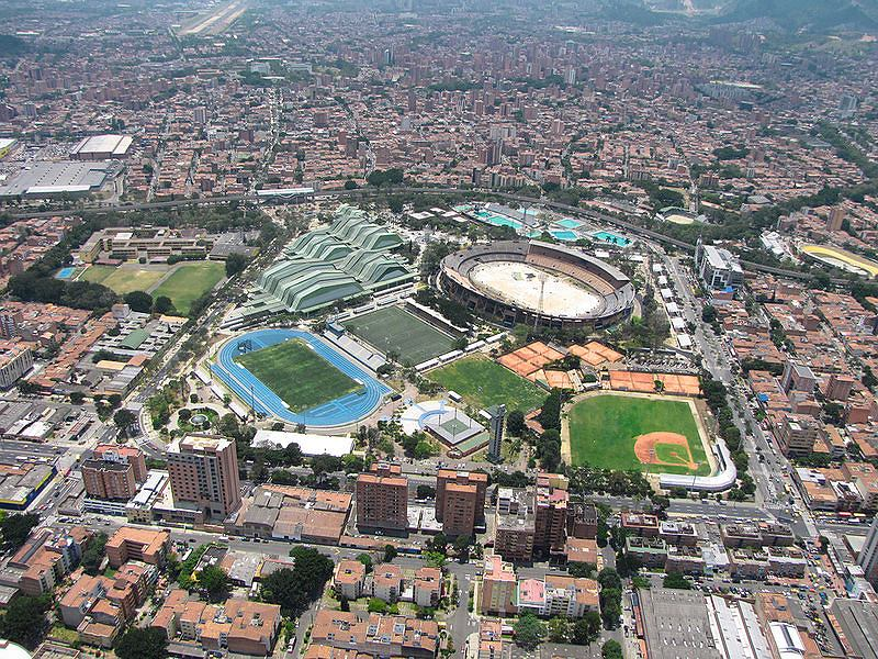 Widok Medellin z lotu ptaka. Widać stadion lekkoatletyczny, stadion piłkarski, stadion do baseballa, a w tle o pofałdowanym dachu - kompleks hal Atanasio Girardot