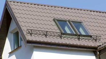 Płotek przeciwśnieżny zamontowany na dachu krytym blachodachówką, dopasowany kolorystycznie do pokrycia