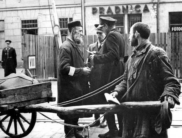 Warszawskie getto na początku 1941 r. Polski granatowy policjant w towarzystwie żydowskiego funkcjonariusza kontrolują przechodniów. W podległej Niemcom policji podczas okupacji służyło kilkanaście tysięcy Polaków