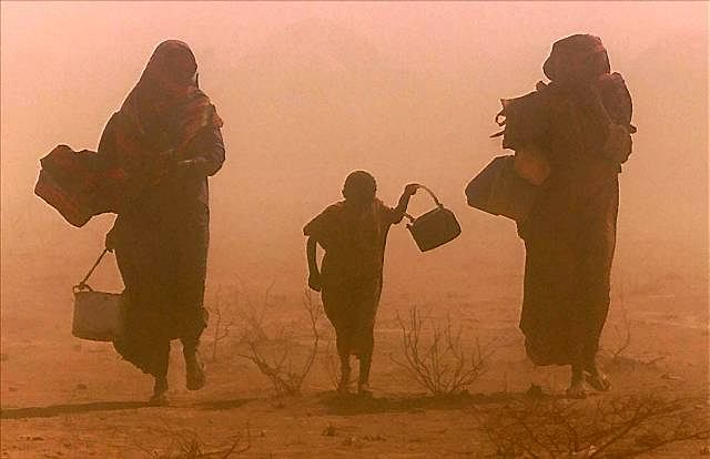 Etiopia, kwiecień 2000 r. Na zdjęciu ludzie, którzy musieli uciekać ze swoich wiosek, po klęsce suszy. Idą w burzy piaskowej w etiopskiej prowincji Denan.