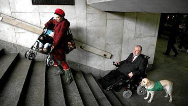 W Polsce budynki użyteczności publicznej nie są dostępne dla niepełnosprawnych. Na zdjęciu: niepełnosprawny Marek Sołtys próbuje się wydostać z Dworca Centralnego w Warszawie. Z wózkiem Patrycja Dołowy z fundacji Mama