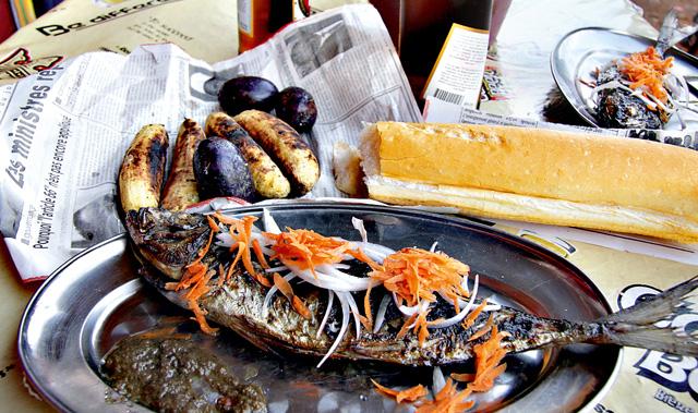 Kamerun - Grillowana ryba z pikantnym sosem i cebulą i grillowane plantany ze śliwkami, podane na porannej gazecie.