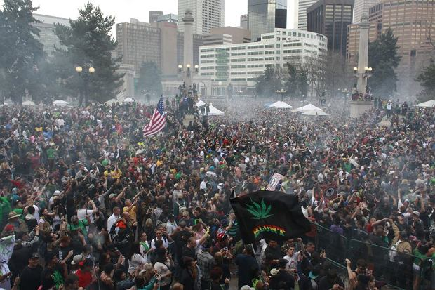 Members of a crowd numbering tens of thousands smoke marijuana simultaneously at 4:20 PM, at the Denver 420 pro-marijuana rally at Civic Center Park in Denver on Saturday, April 20, 2013. Even before the passage in November 2012 of Colorado Amendment 64 promised the legalization of marijuana for recreational use, April 20th has for years been a celebration of marijuana counterculture, and the 2013 rally draw larger crowds than previous years. (AP Photo/Brennan Linsley)