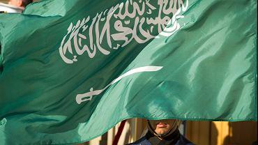 Saudyjscy kaci w ciągu jednego dnia ścięli kilkadziesiąt osób, a jednego ze skazańców ukrzyżowali - obrońcy praw człowieka alarmują, że ortodoksyjne królestwo coraz hojniej szafuje wyrokami śmierci. Na zdjęciu członek gwardii honorowej i saudyjska flaga.