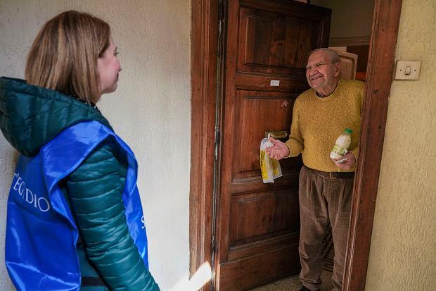 Wolontariuszka z organizacji  Sant' Egidio przynosi podstawowe produkty spożywcze starszemu mieszkańcowi Rzymu, 9 marca 2020 r.