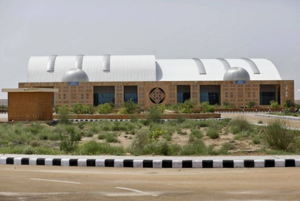 Departure and arrival sections are pictured at the Jaisalmer Airport in desert state of Rajasthan, India, August 13, 2015. Two-and-a-half years after the completion of a new $17 million terminal building, the airport in Jaisalmer, a small and remote desert city in India's western Rajasthan state, stands empty. Not a single passenger has passed through the gates of an airport big enough to handle more than 300,000 travellers a year, with parking bays for three 180-seater narrow-body jets. India has spent more than $50 million since 2009 on eight airports that do not receive scheduled flights - white elephants that are a reminder of the pitfalls for Prime Minister Narendra Modi as he bets on an infrastructure drive to fuel growth. Picture taken August 13, 2015.  REUTERS/Anindito Mukherjee