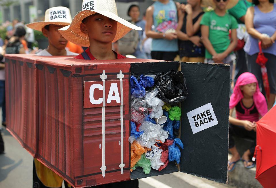 Filipińscy aktywiści działający na rzecz ochrony środowiska demonstrują przed siedzibą kanadyjskiej ambasady przeciwko niedozwolonym kontenerom ze śmieciami z tego kraju, które od 2013 r. tkwią w porcie. Mają na sobie wypełnione odpadkami konstrukcje przypominające owe kontenery. Manila, 7 maja 2015 r.  Między Kanadą a Filipinami trwa wojna o śmieci. Konflikt wybuchł w 2013 r., gdy Kanada wysłała tony swoich plastików na Filipiny. Dziesiątki kontenerów, m.in. z zużytymi pampersami dla dorosłych, czekają do dziś w porcie w Manili na rozładowanie. By skłonić Filipiny do przyjęcia odpadów zapewniono, że zawierają plastik nadający się do utylizacji. Na zdjęciu: demonstracja w Mannili. Filipiny, 7 maja 2015