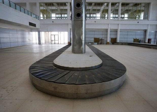 A baggage carousel is pictured inside the Jaisalmer Airport in desert state of Rajasthan, India, August 13, 2015. Two-and-a-half years after the completion of a new $17 million terminal building, the airport in Jaisalmer, a small and remote desert city in India's western Rajasthan state, stands empty. Not a single passenger has passed through the gates of an airport big enough to handle more than 300,000 travellers a year, with parking bays for three 180-seater narrow-body jets. India has spent more than $50 million since 2009 on eight airports that do not receive scheduled flights - white elephants that are a reminder of the pitfalls for Prime Minister Narendra Modi as he bets on an infrastructure drive to fuel growth. Picture taken August 13, 2015. REUTERS/Anindito Mukherjee      TPX IMAGES OF THE DAY