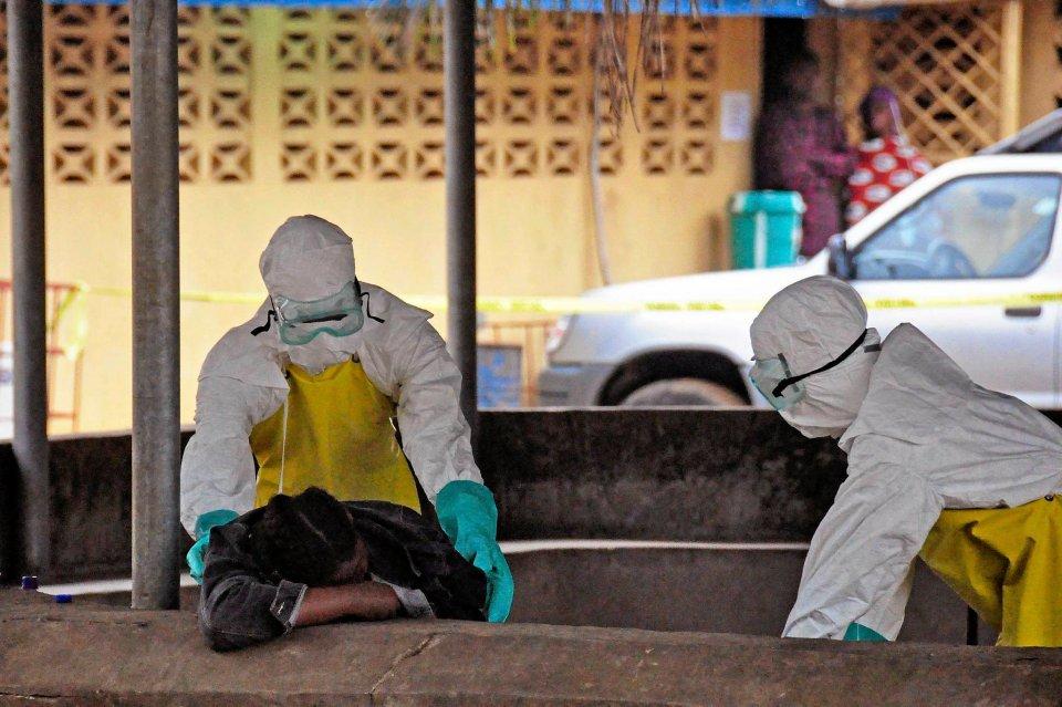 Walka z wirusem spowodowała zapaść opieki medycznej w Liberii. Cierpią zakażeni ebolą, ale też inni chorzy. Lekarze są przytłoczeni ilością pracy. Z każdym tygodniem maleje liczba ochotników, którzy chcą opiekować się chorymi. NA ZDJĘCIU: Sanitariusze zabierają ciało swojego znalezionego na ławce kolegi. Najprawdopodobniej zmarł po zarażeniu ebolą.