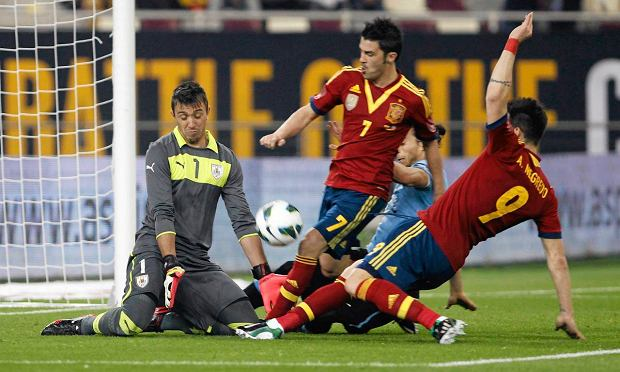 Uruguay's Frenando Muslera (L) fights for the ball with Spain's David Villa (C) and Alvaro Negredo (R) during their international friendly soccer match in Doha February 6, 2013.REUTERS/Mohammed Dabbous (QATAR - Tags: SPORT SOCCER) SLOWA KLUCZOWE: :rel:d:bm:GF2E9261KZE01