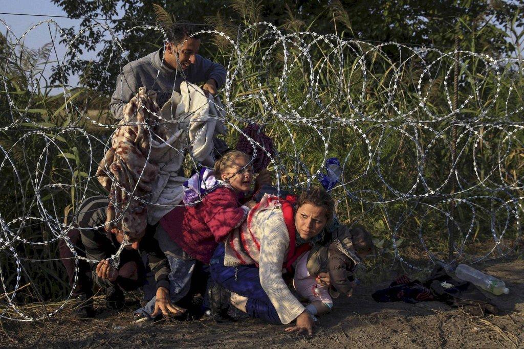 Uchodźcy z Syrii przedzierają się przez zasieki na granicy z serbsko-węgierskiej