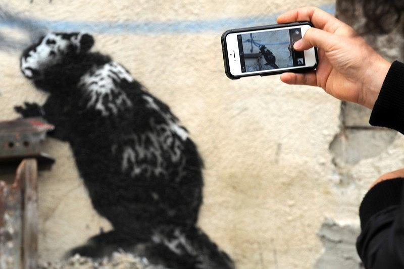 Banksy, brytyjski mistrz street artu, którego tożsamość - mimo sławy - pozostaje nieznana, podbija Nowy Świat. W ramach swojego nowego projektu przez cały październik anonimowy artysta będzie zamieszczał na terenie miasta nowe pracy. Jak do tej pory na ścianach nowojorskich budynków pojawiły się grafiki Banksy'ego, a na ulicach - m.in. ciężarówka z pluszowymi zwierzątkami oraz stragan z autentycznymi pracami artysty, które można było kupić za bezcen. Czym jeszcze zaskoczy Banksy? . Na zdjęciu: przechodzień fotografujący jedną z grafik Banksy'ego, namalowaną we wschodniej części miasta.