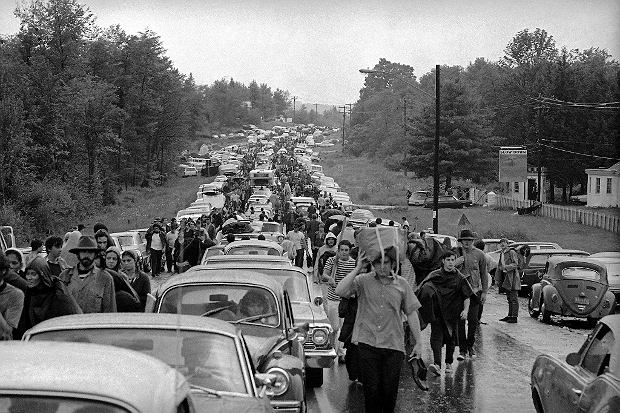 FILE - In this Aug. 16, 1969 file photo, hundreds of rock music fans jam a highway leading from Bethel, N.Y., as they try to leave the Woodstock Music and Art Festival. More than 400,000 people attended Woodstock which was staged 80 miles northwest of New York City on a bucolic hillside owned by dairy farmer Max Yasgur. It was great spot for peaceful vibes, but miserable for handling the hordes coming in by car. Fifty years later, memories of the rainy weekend Aug. 15-18, 1969 remain sharp among people who were in the crowd and on the stage. (AP Photo, File) SLOWA KLUCZOWE: Walking Holding Crowded Transportation Traffic