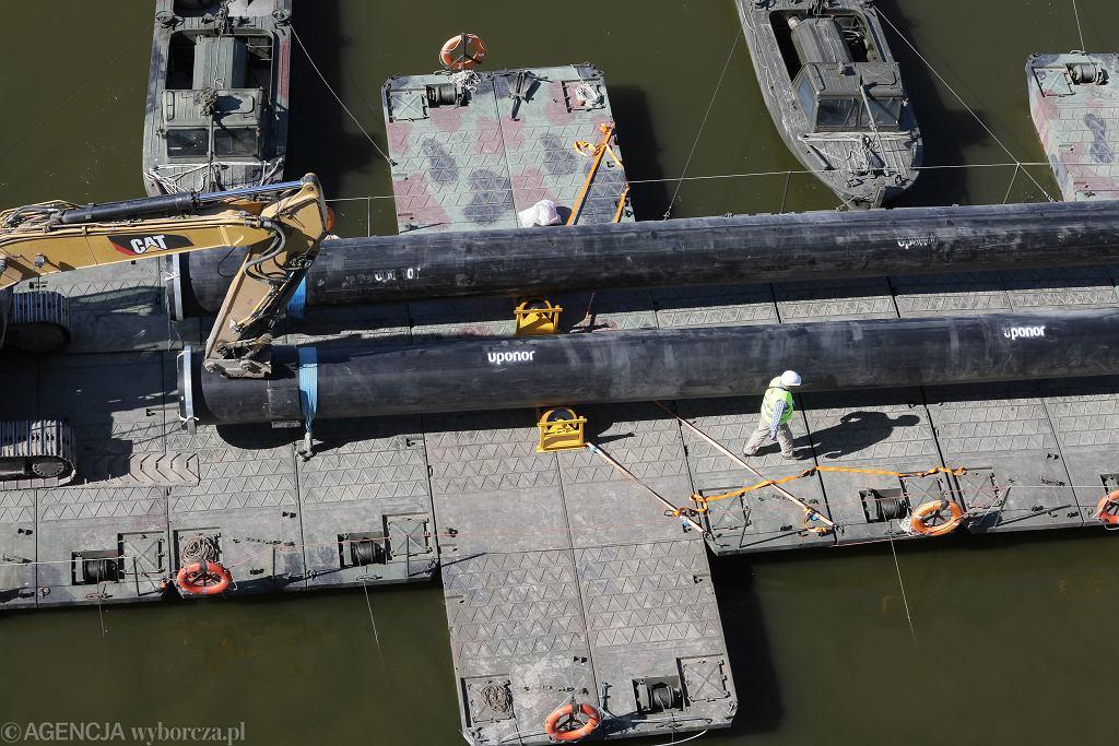 Układanie tymczasowego rurociągu ściekowego na moście pontonowym w związku z awaria kolektora ściekowego pod dnem Wisły