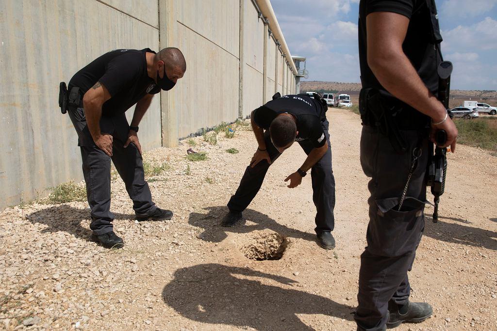 Policjanci i strażnicy więzienni oglądają dziurę przez, którą uciekli zbiegli Palestyńczycy z więzienia Gilboa, Izrael, 6 września 2021 r.