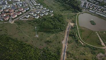 Po lewej Zakoniczyn. Centralnie asfaltowa droga od centrum edukacyjnego do zbiornika retencyjnego