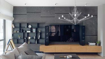 Efektowana, rozrzeźbiona ściana za telewizorem wykończona jest bazaltem. Półki zrobiono ze spawanej, cienkiej blachy. Z rysunkiem półek współgra koronkowa geometria lampy Lightweight, proj. Toma Dixona, Foscarini.