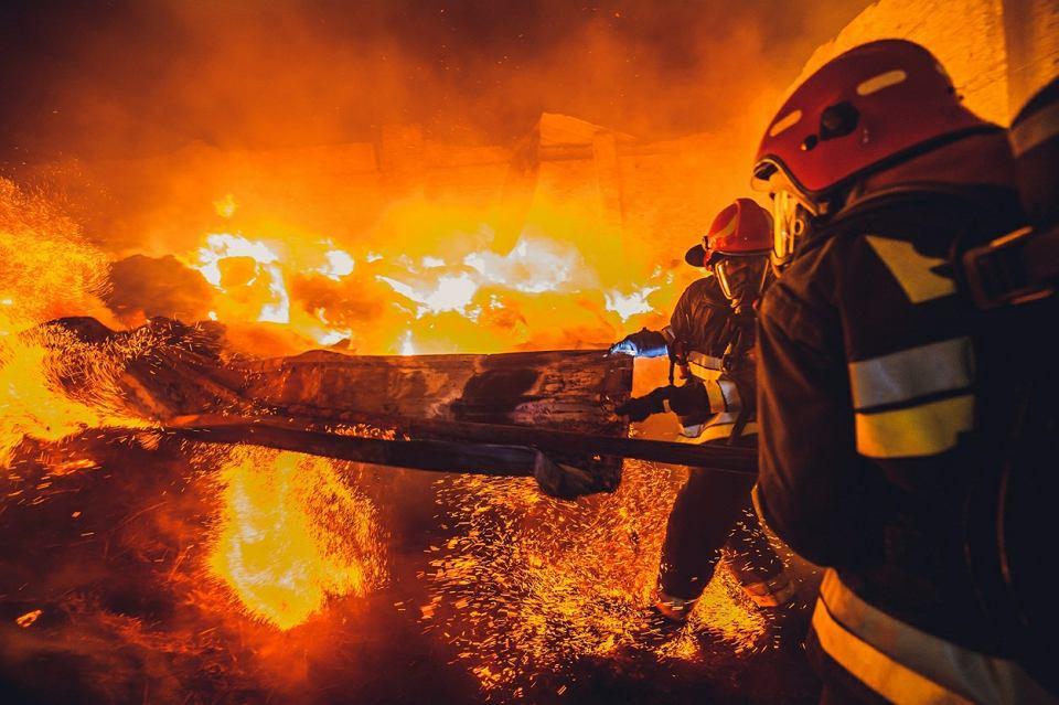 Pożar w Ośrodku Jeździeckim Zbrosławice, strażacy usuwają elementy blachy z zawalonego dachu, żeby stworzyć dostęp do płonącego budynku, 16 listopada 2016 r.