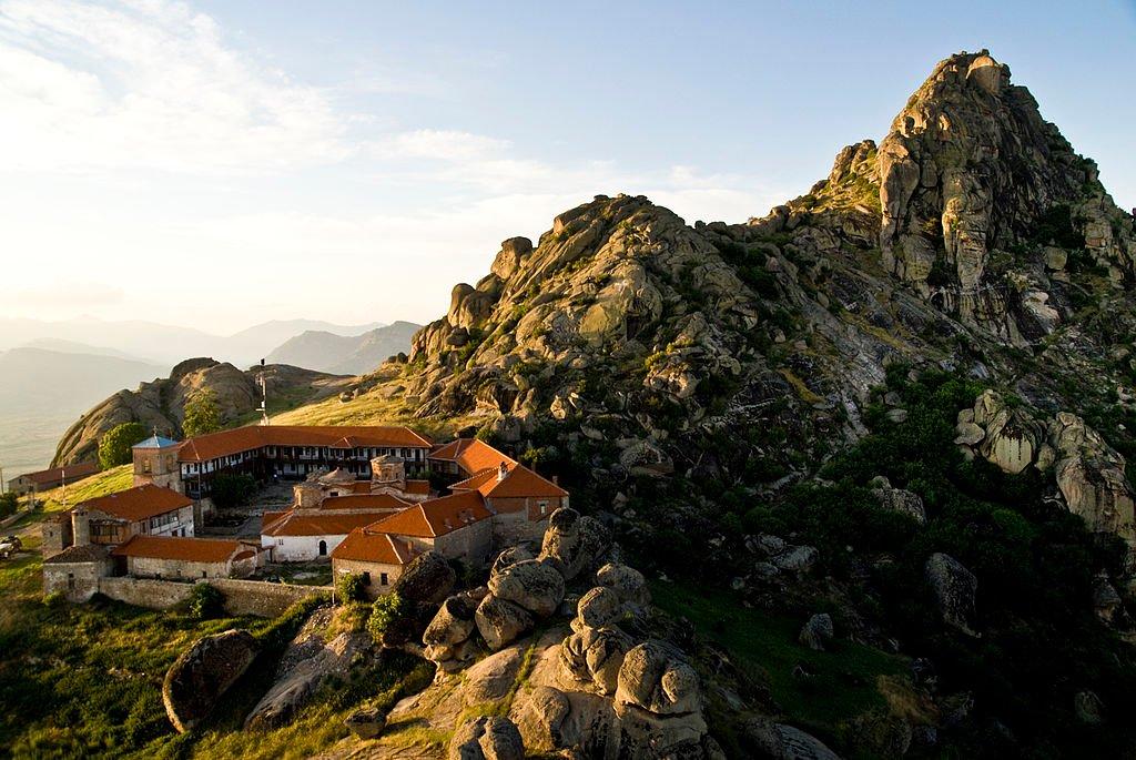 Budynki sakralne Macedonii to największy skarb tego kraju. Położone malowniczo na zboczach gór, wykończone z niezwykłą precyzją są wspaniale zachowanym przykładem sztuki bizantyjskiej. Wiele z nich oferuje także miejsca noclegowe, a wraz z nimi unikalne przeżycie. Prezentujemy Wam macedońskie kościoły i monastyry, które zadziwiają swoim pięknem i położeniem, a także podpowiadamy, w których z nich możecie zanocować. Z okna naszego pokoju rozciągał się wspaniały widok na okoliczne szczyty, wokół panowała cisza, którą zakłócały jedynie cykady. Strudzeni podróżą, położyliśmy głowy na poduszkach i już w zasadzie było rano. O 6 przyszedł do nas pop, żeby zaprosić na nabożeństwo. Oczywiście skrócone, bo reszta brała w nim udział już od godziny. Staliśmy pośród groźnych ikon zerkających na nas z każdej możliwej strony, wokół rozbrzmiewały pieśni w niezrozumiałym języku. Po mszy wyszliśmy na zewnątrz, żeby ochłonąć. Wokół pustkowie, górskie krajobrazy, cisza i spokój. Tak wyglądała nasza noc w monastyrze sv. Jovana Bigorskiego (Jana Chrzciciela). Nie trzeba być religijnym, żeby docenić takie przeżycie. Kościoły i monastyry to prawdziwy skarb Macedonii. Dobrze zachowane budynki odzwierciedlają duchową i artystyczną spuściznę bizantyjskiej tradycji. Oprócz tego, że wszystkie posiadają cechy charakterystyczne dla bizantyjskiej architektury, mają także unikalne, wyjątkowo szczegółowe drewniane rzeźbienia, wykonane przez mistrzów starej, macedońskiej szkoły sztuki eklezjastycznej. Do niektórych naprawdę niełatwo się dostać, część z nich zbudowana została na stromych zboczach odległych gór. Wszystkie natomiast nadal zachwycają, a wiele z nich oferuje także możliwość noclegu.