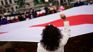 Historyczna, nieuznawana przez reżim Aleksandra Łukaszenki, biało-czerwono-biała flaga Białorusi na wiecu poparcia dla  białoruskiej opozycji przed siedzibą Parlamentu Europejskiego. Bruksela, 25 marca 2021 r.