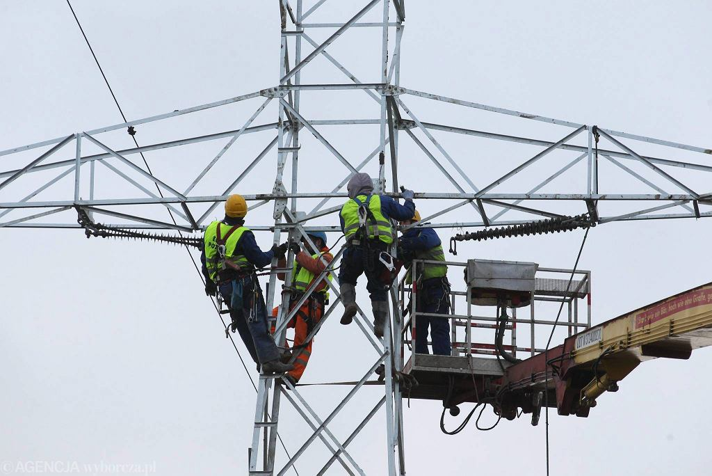Energetycy pracujący na słupie linii energetycznej. Zdjęcie ilustracyjne