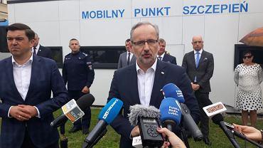 Zamość. Minister Adam Niedzielski podczas konferencji prasowej. W tle podpalony mobilny punkt szczepień