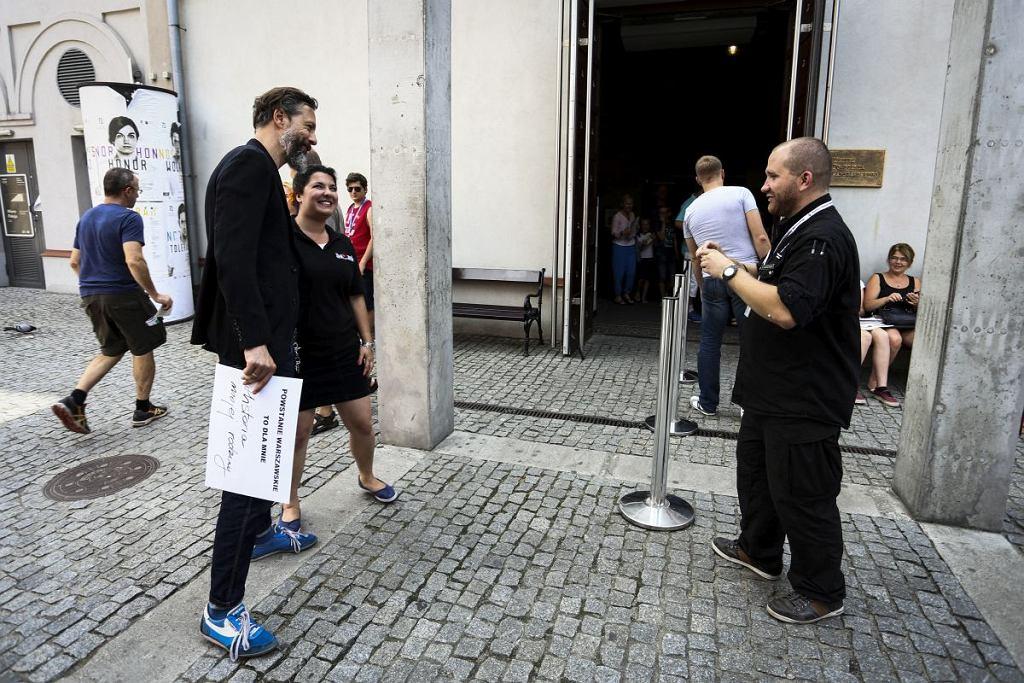 Szymon Majewski pozuje do zdjęcia z jedną z dziewczyn pracujących w Muzeum Powstania Warszawskiego