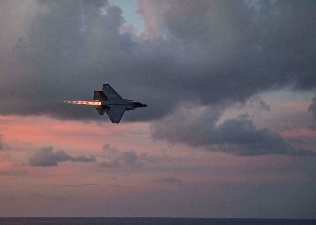 F-35C przelatuje z włączonym dopalaczem obok lotniskowca