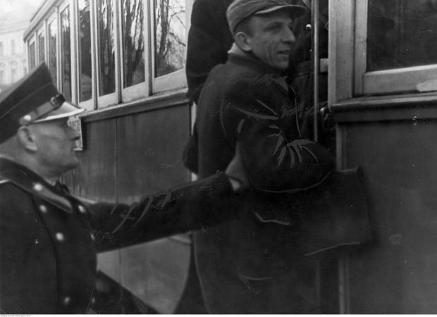 Polski policjant (granatowy) zatrzymuje mężczyznę wskakującego do jadącego tramwaju, marzec 1940 r.