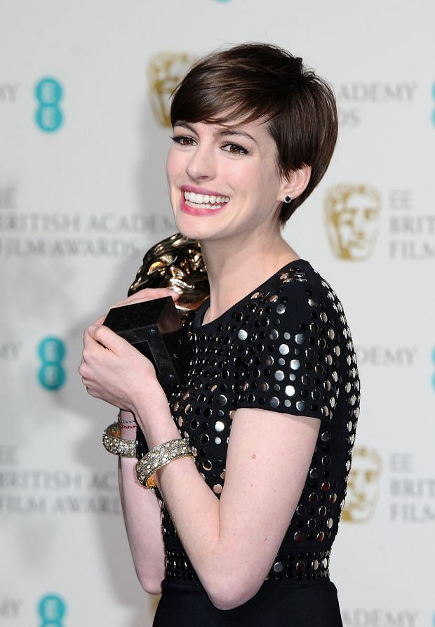 "American actress Anne Hathaway poses backstage with the award for Supporting Actress for her role in ""Les Miserables,"" at the BAFTA Film Awards at the Royal Opera House on Sunday, Feb. 10, 2013, in London. (Photo by Jonathan Short/Invision/AP)"