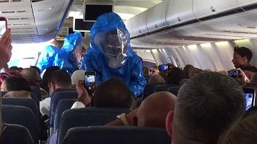 Zespół w kombinezonach ochronnych wchodzi do samolotu, żeby wyprowadzić mężczyznę, który zażartował, że ma ebolę