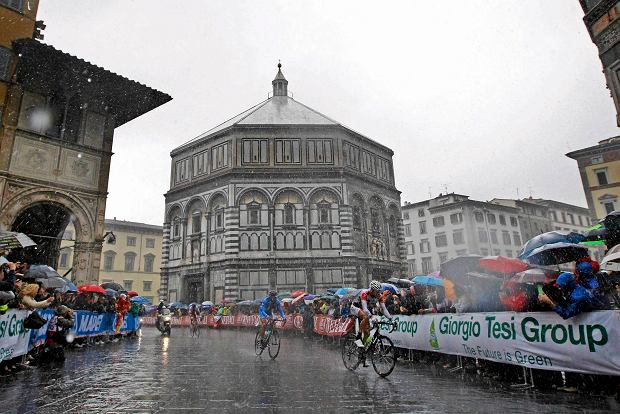 Riders cycle under heavy rain next to the San Giovanni Baptistery during the men's elite road race at the UCI Road World Championships in Florence September 29, 2013. REUTERS/Giampiero Sposito (ITALY - Tags: SPORT CYCLING ENVIRONMENT TRAVEL) SLOWA KLUCZOWE: :rel:d:bm:GF2E99T0X4E01