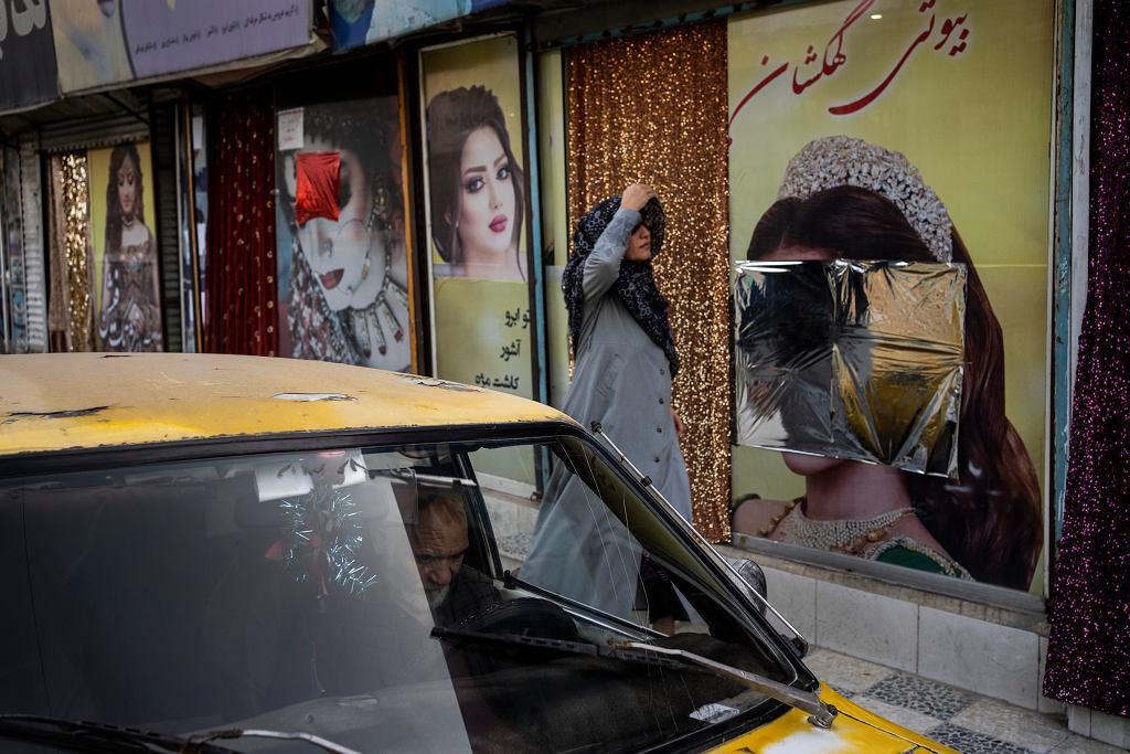 Afganistan. Kobieta przechodzi obok salonu piękności, którego okna zostały zniszczone (co zakryto srebrną i czerwoną folią).