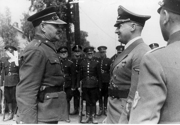 Gubernator Hans Frank (z prawej) przyjmuje meldunek od komendanta oddziału polskiej policji (granatowej). W tle widoczni stojący w dwuszeregu polscy policjanci, październik 1940 r.