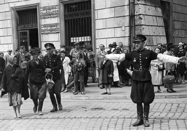 Polski policjant (granatowy) podczas kierowania ruchem ulicznym w Krakowie. Widoczny również policjant przeprowadzający przez ulicę kobietę i mężczyznę, lipiec 1941 r.